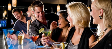 Guy speaking with a girl and her two friends in a bar