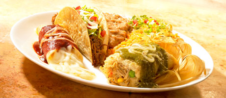 Full platter of Mexican food, including encilada, hard shell shredded beef taco and a tamale